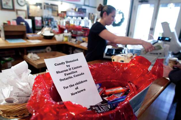A sign at the Newtown General Store offers candy for the children of Newtown on Saturday, December 22, 2012. Another sign in the business said all hot drinks were paid for by a donor from New York. The outpouring of support and gifts from around the world has been appreciated by thankful residents. Photo: Joshua Trujillo, Joshua Trujillo/Hearst Newspaper / The News-Times