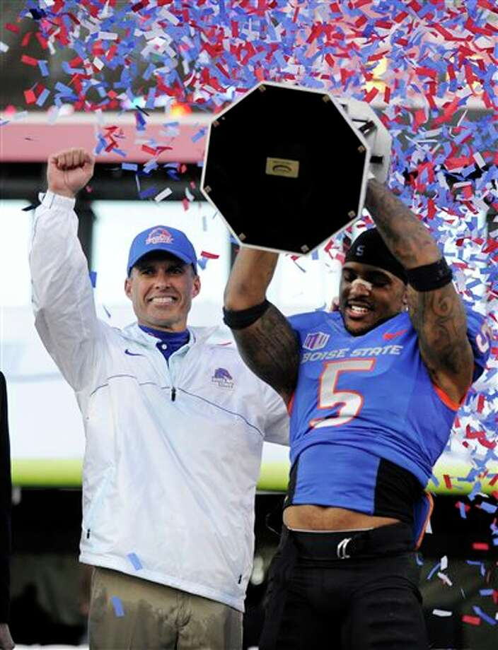 Boise State coach Chris Peterson, left, gestures as cornerback Jamar Taylor holds the championship trophy after the MAACO Bowl NCAA college football game against Washington, Saturday, Dec. 22, 2012, in Las Vegas. Boise State defeated Washington 28-26. Photo: David Becker, AP / FR170737 AP