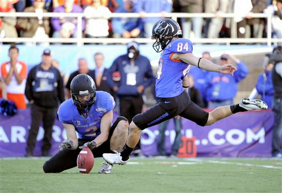 Boise State Matt Miller (2) holds the ball for kicker Michael Frisina (84) who boots the ball during the final minutes of the MAACO Bowl NCAA college football game on Saturday, Dec. 22, 2012, in Las Vegas. The field goal was the go-ahead for Boise State to defeat Washington 28-26. Photo: David Becker, AP / FR170737 AP
