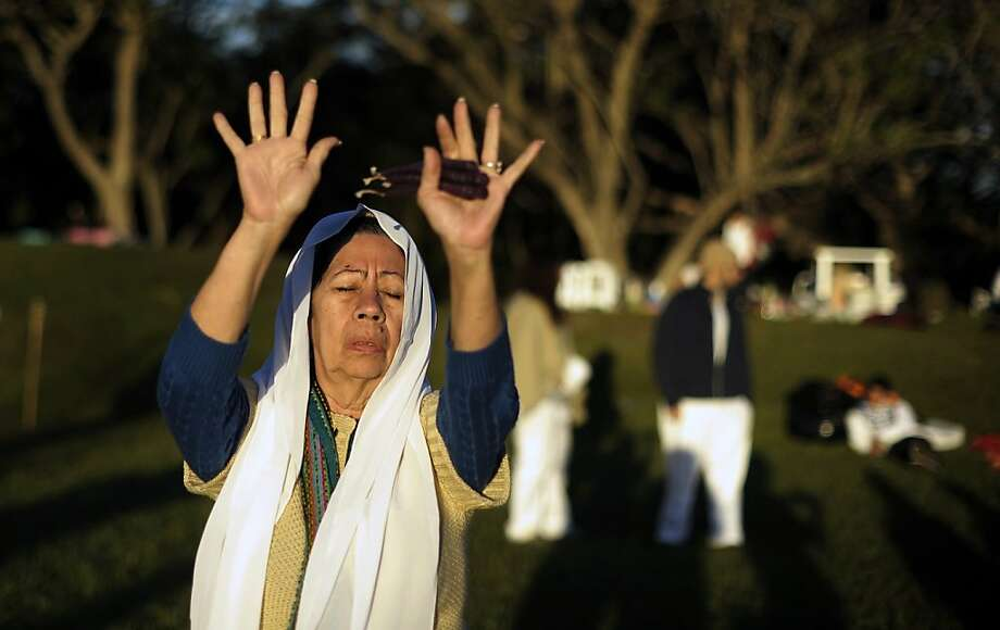 A woman prays to welcome dawn during the fire ceremony at the San Andres Archeological site in the town of Opico 32 Kms. west from San Salvador, El Salvador on December 22, 2012 at the end of the celebration of the Baktun 13. Jose CABEZAS/AFP/Getty Images Photo: Jose Cabezas, AFP/Getty Images