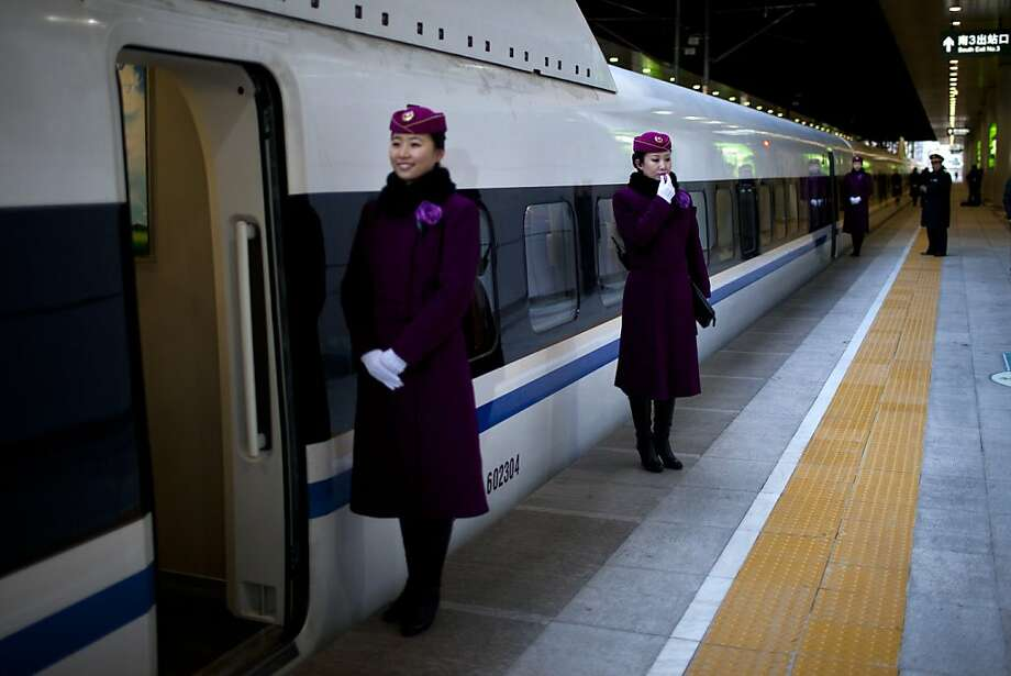 A bullet train attendant, center, checks her microphone while other attendants wait for invited journalists to board a CRH high-speed train at Beijing's West Railway Station, China, Saturday, Dec. 22, 2012. Chinese government invited journalists Saturday to board a bullet train for a test run on a part of Beijing-Guangzhou high-speed railway line, the world's longest high-speed rail line that is scheduled to open on Dec. 26, 2012. (AP Photo/Alexander F. Yuan) Photo: Alexander F. Yuan, Associated Press