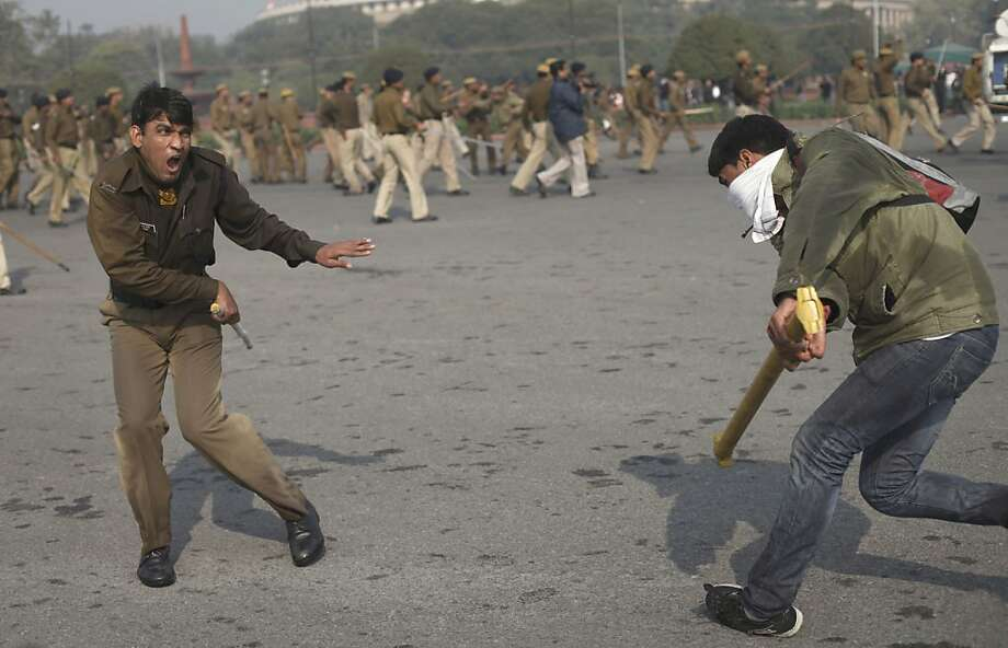 An Indian student tries to hit a policeman with an iron rod during a protest in New Delhi, India, Saturday, Dec. 22, 2012. Police used tear gas and water cannons to push back thousands of people who tried to march to the presidential mansion to protest the recent gang rape and brutal beating of a 23-year-old student on a moving bus. (AP Photo/Altaf Qadri) Photo: Altaf Qadri, Associated Press