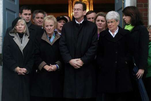 ADDS NAME OF OFFICIAL - Connecticut Gov. Dan Malloy, center, stands with Janet Robinson, left, the Newtown Superintendent of  Schools  and other officials to observe a moment of silence while bells ring 26 times in Newtown, Conn., Friday, Dec. 21, 2012, in honor of the 26 adults and children who were killed last Friday during the shooting at Sandy Hook Elementary School. (AP Photo/Seth Wenig) Photo: Seth Wenig, Associated Press / Associated Press