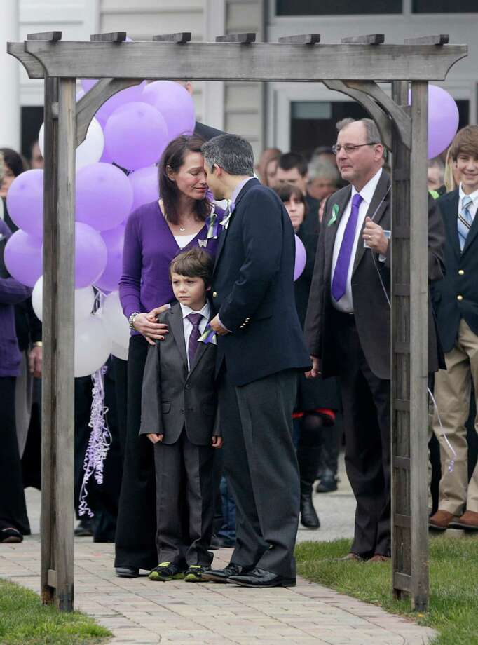 While their son Jake Hockley stands between them, Nicole Hockley and her husband Ian Hockley touch their heads together at the end of a funeral service for their son Dylan Hockley in Bethel, Conn., Friday, Dec. 21, 2012. Dylan Hockley, 6, was killed when Adam Lanza walked into Sandy Hook Elementary School in Newtown, Conn., Dec. 14, and opened fire, killing 26 people, including 20 children, before killing himself. (AP Photo/Seth Wenig) Photo: Seth Wenig, Associated Press / Associated Press