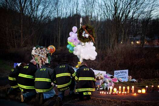 Firefighters kneel together in front of a makeshift memorial for the victims of the Sandy Hook Elementary School shooting, near the school's entrance in Newtown, Conn., Dec. 15, 2012. Connecticut's chief medical examiner said Saturday it appeared that all of the children killed at the elementary school had been shot with a long rifle, as new and tragic details about the massacre of 26 people Friday emerged. (Marcus Yam/The New York Times) Photo: MARCUS YAM, New York Times / Associated Press