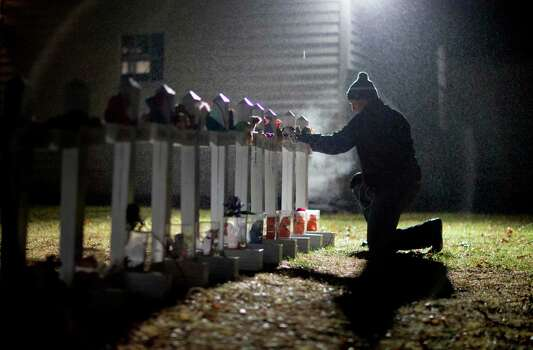 Frank Kulick, adjusts a display of wooden crosses, and a Jewish Star of David, representing the victims of the Sandy Hook Elementary School shooting, on his front lawn, Monday, Dec. 17, 2012, in Newtown, Conn. (AP Photo/David Goldman) Photo: David Goldman, Associated Press / Associated Press