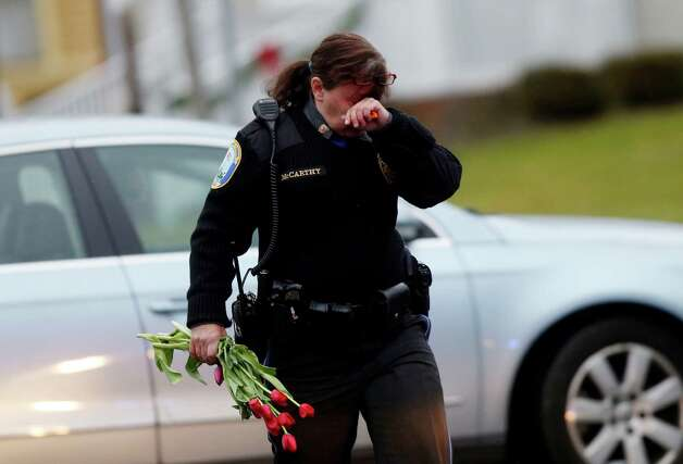 Newtown Police Officer Maryhelen McCarthy carries flowers near a memorial for shooting victims Sunday, Dec. 16, 2012 in Newtown, Conn.  A gunman walked into Sandy Hook Elementary School in Newtown, Friday and opened fire, killing 26 people, including 20 children. The flowers and other items were taken to nearby Saint Rose of Lima Roman Catholic Church. (AP Photo/Jason DeCrow) Photo: Jason DeCrow, Associated Press / Associated Press
