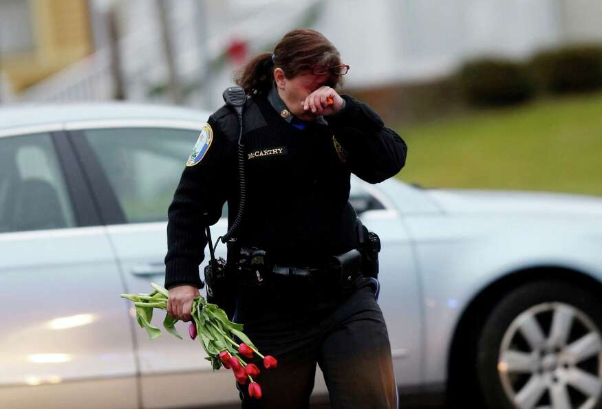 Newtown Police Officer Maryhelen McCarthy carries flowers near a memorial for shooting victims Sunda
