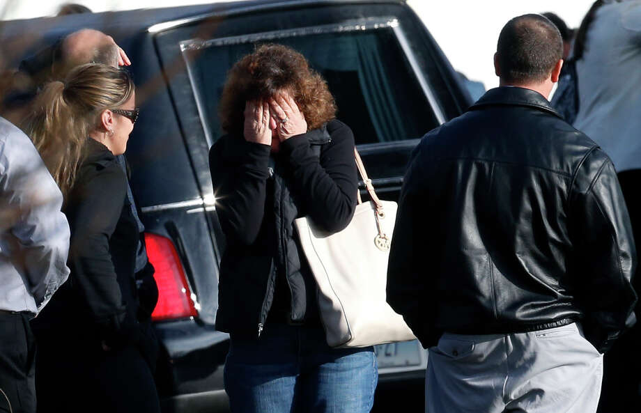 A woman reacts as a hearse begins to pull out outside of St. Rose of Lima Roman Catholic Church after funeral services for Jessica Rekos, Tuesday, Dec. 18, 2012, in Newtown, Conn. Rekos, 6, was killed when Adam Lanza walked into Sandy Hook Elementary School in Newtown, Dec. 14, and opened fire, killing 26 people, including 20 children, before killing himself. (AP Photo/Julio Cortez) Photo: Julio Cortez, Associated Press / Associated Press