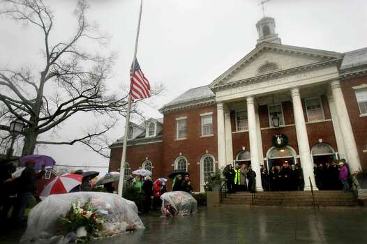 Officials including Connecticut Governor Dan Malloy observe a moment of silence on the steps of Edmond Town Hall while bells ring 26 times in Newtown, Conn., Friday, Dec. 21, 2012.   The chiming of bells reverberated throughout Newtown, commemorating one week since the crackle of gunfire in a schoolhouse killed 20 children and six adults in a massacre that has shaken the community and the nation. (AP Photo/Seth Wenig) Photo: Seth Wenig, Associated Press / Associated Press