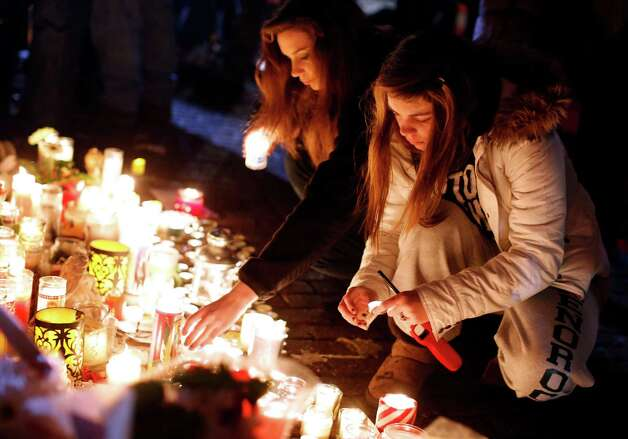 Visitors light candles at a memorial to shooting victims, Monday, Dec. 17, 2012, in Newtown, Conn. A gunman walked into Sandy Hook Elementary School in Newtown Friday and opened fire, killing 26 people, including 20 children. (AP Photo/Jason DeCrow) Photo: Jason DeCrow, Associated Press / Associated Press