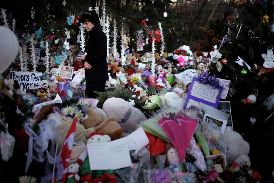 Jeanne Walker of Newtown walks through an overflowing memorial to the shooting victims in the Sandy Hook village of Newtown, Conn., Thursday, Dec. 20, 2012.   Adam Lanza walked into Sandy Hook Elementary School in Newtown,  Dec. 14, and opened fire, killing 26 people, including 20 children, before killing himself. (AP Photo/Seth Wenig) Photo: Seth Wenig, Associated Press / Associated Press