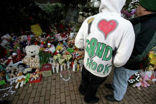 A Sandy Hook resident wears a handmade sweatshirt in support of his town while looking at a memorial to the Newtown shooting victims in the Sandy Hook village of Newtown, Conn., Saturday, Dec. 22, 2012.  The funerals for the victims of the school shooting are wrapping up after a wrenching week of farewells. Twenty children and six adults were killed at Sandy Hook Elementary School on Dec. 14.  Adam Lanza, the lone gunman, killed his mother before going on the rampage and then committed suicide. (AP Photo/Seth Wenig) Photo: Seth Wenig, Associated Press / Associated Press
