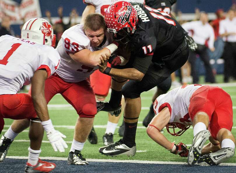 Katy defensive lineman Cody Gessler (93) tries to keep Cedar Hill quarterback Damion Hobbs (11) from