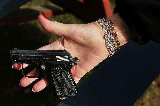 BRIDGEPORT, CT - DECEMBER 22:  A woman holds a Beretta pistol at a gun buyback event at the Bridgeport Police Department's Community Services Division on December 22, 2012 in Bridgeport, Connecticut. The buyback program, the largest in the city's history, will offer up to $200 value for a working handgun, $75 for a rifle and a higher rate of payment for a weapon determined to be an assault-type rifle. There was strong turnout for the event with many residents turning in guns they haven't used in years. Following the massacre of children and adults at a school in Newtown, Connecticut last week, numerous Connecticut towns and cities are trying to get more guns off the street. Photo: Spencer Platt, Getty Images / 2012 Getty Images