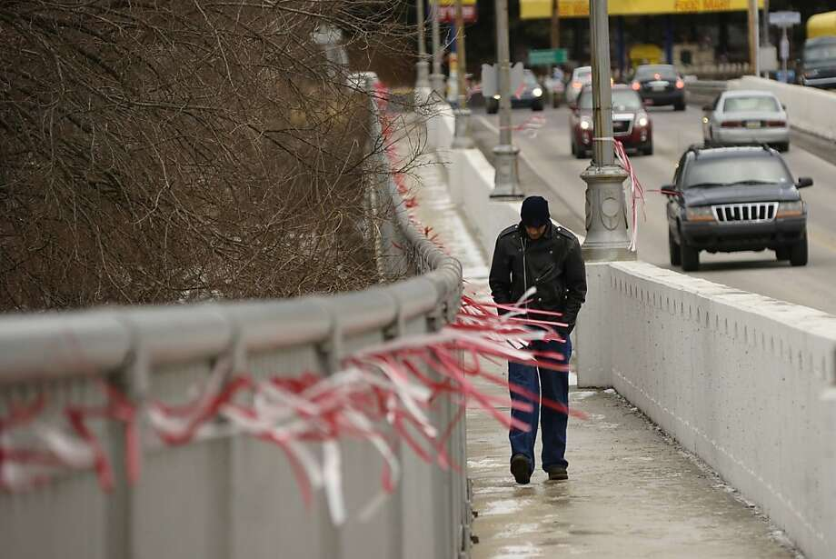A man walks across a bridge in Mount Carmel, Pa., as winds blow Saturday, Dec. 22, 2012. (AP Photo/The News-Item, Larry Deklinski) Photo: Larry Deklinski, Associated Press