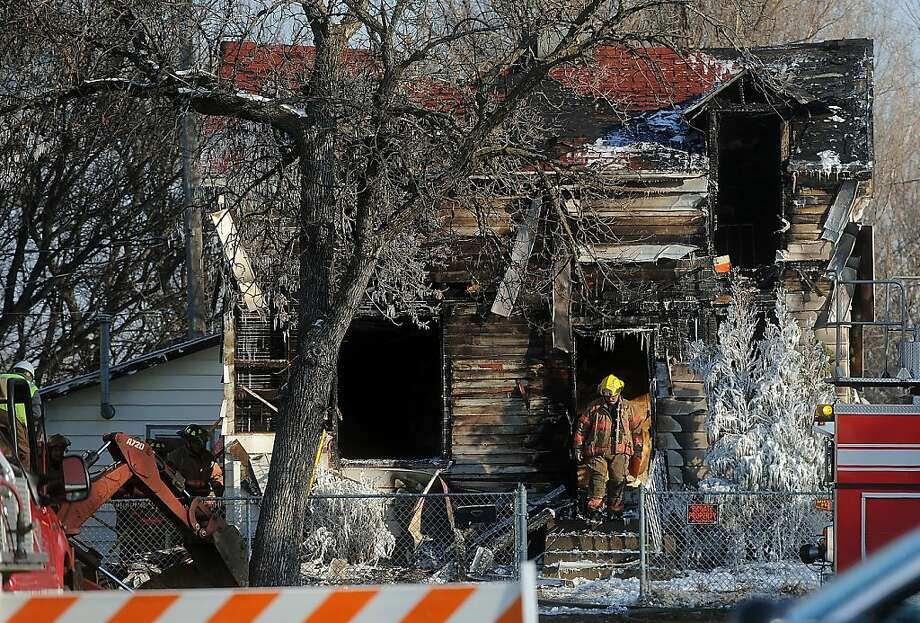 A Sioux Falls firefighter exits the remains of the home at Brookings and Main Ave. in northern Sioux Falls, S.D. on Saturday, Dec. 22, 2012. A fire that tore through a home in Sioux Falls on Saturday morning killed three children and sent two adults to the hospital, leaving a neighborhood in mourning just days before Christmas. (AP Photo/The Argus Leader, Jay Pickthorn) Photo: Jay Pickthorn, Associated Press