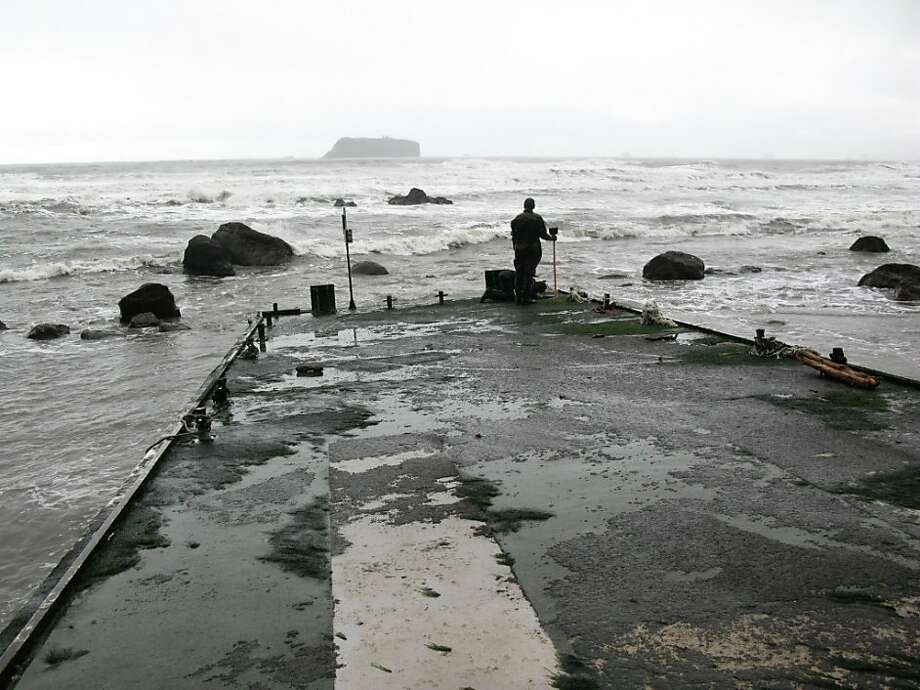A member of the Washington tsunami debris experts team stands on a dock Friday Dec. 21, 2012 that apparently floated from Japan after last year's tsunami and just washed ashore on a Washington beach near Forks Tuesday. (AP Photo/Washington Dept. of Fish & Wildlife) Photo: Associated Press