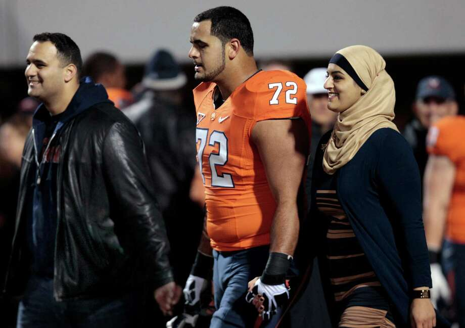 FILE - This Nov. 15, 2012, file photo, shows Virginia offensive tackle Oday Aboushi and his family as they are introduced prior to an NCAA college football game at Scott stadium in Charlottesville, Va. The big offensive lineman, a potential first-round pick in the NFL draft in April, returned to Staten Island on Saturday, Dec. 22, 2012 to try to lend a helping hand to those affected by the storm _ some of them his friends and neighbors. (AP Photo/Steve Helber, File) Photo: Steve Helber