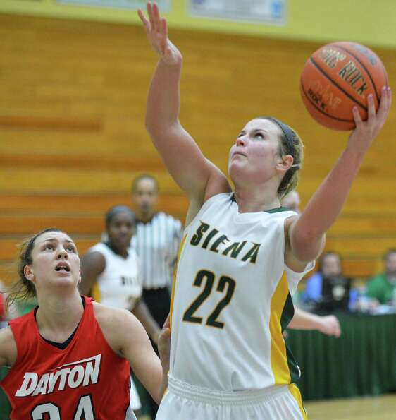 Siena's #22 Lily Grenci gets a shot past Dayton's #24 Andrea Hoover, left, during Saturday's game at