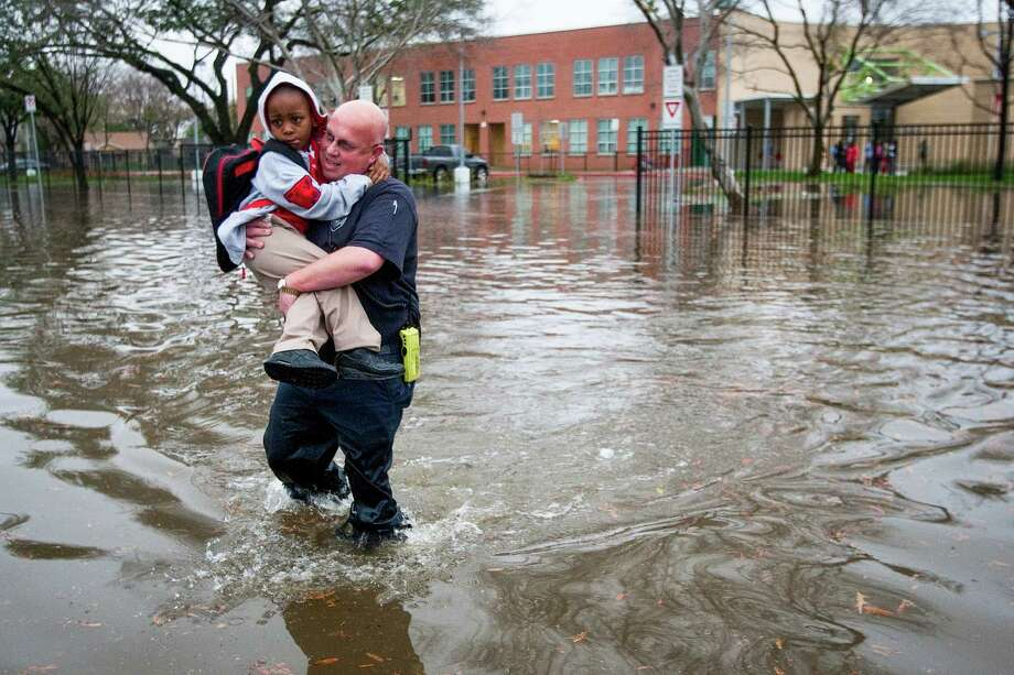 Houston firefighter Scotch Blair carries Dezmund Chapman, 5, through floodwaters to his parents after heavy rain flooded the streets around Peck Elementary Monday, Jan. 9, 2012, in Houston. Photo: Brett Coomer, Houston Chronicle / © 2012 Houston Chronicle