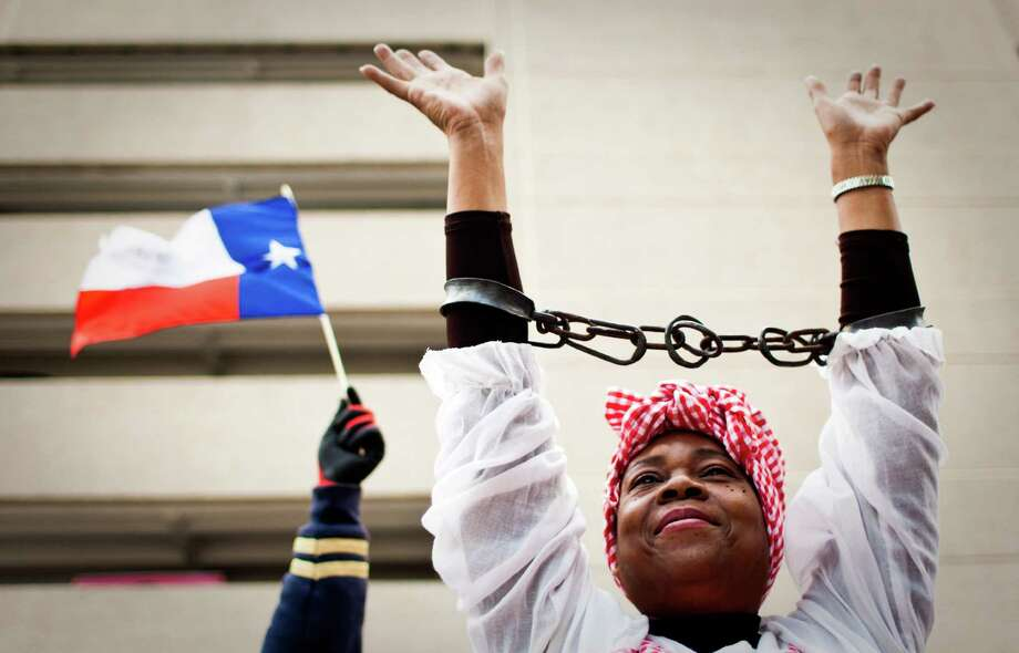 "Candi Flora, a historian wearing actual irons from the days of slavery, rides on a pick up sponsored by the Greater Houston Fair Housing Center during the 34th Annual ""Original"" Dr. Martin Luther King Birthday Parade and Celebration Monday, Jan. 16, 2012, in Houston. Photo: Nick De La Torre, Houston Chronicle / © 2012  Houston Chronicle"