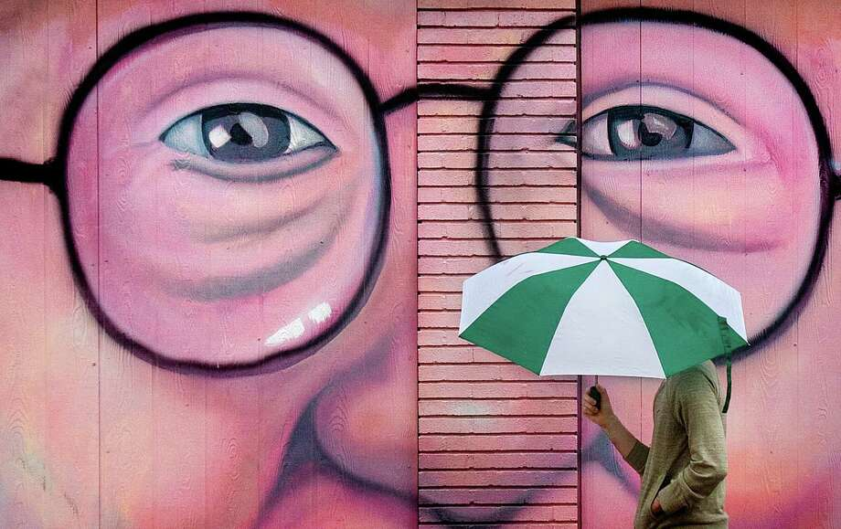 Eric Venner takes shelter under an umbrella as he walks in front of a mural on Holman Street Monday, Jan. 30, 2012, in Houston. Photo: Cody Duty, Houston Chronicle / © 2011 Houston Chronicle