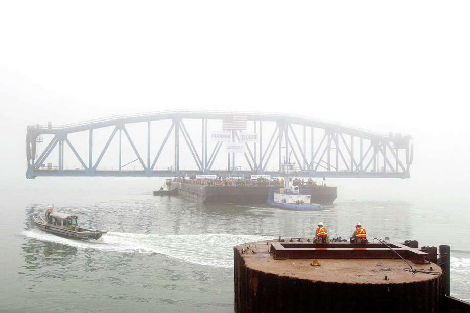 Workers wait in the fog during the float in of the new Galveston Causeway Railroad Bridge Tuesday, Feb. 14, 2012, in Galveston. The New Galveston Causeway Railroad Bridge is an 382 foot span bridge to replace the old 125 foot span bridge which was built from 1909 to 1912 and connects Galveston to the mainland. Photo: James Nielsen, Chronicle / © 2011 Houston Chronicle
