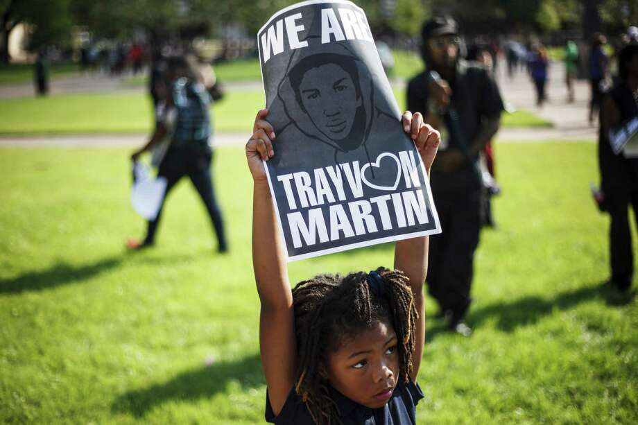 Cedricia McCoy, 7, holds a sign as supporters gather in solidarity for Florida teenager Trayvon Martin who was fatally shot by a neighborhood watch volunteer last month, during a rally at the Sterling Student Life Center at Texas Southern University, Monday, March 26, 2012, in Houston. Photo: Michael Paulsen, Houston Chronicle / © 2012 Houston Chronicle