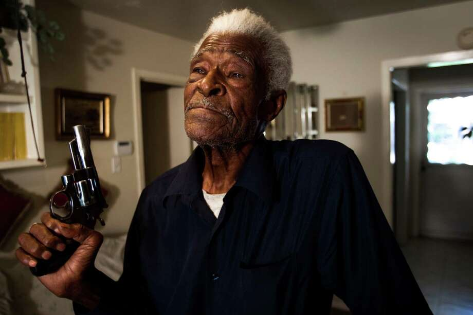 Jack Hands, 92, stands in his living room holding the revolver recently returned to him by police Friday, April 6, 2012, in Houston. Hands was just 90 years old when he fatally shot a much-younger man who threatened him during an altercation in his northeast Houston home. The handgun was one of two weapons involved in the 2010 incident that was confiscated by authorities. A grand jury reviewed the case and cleared the World War II-era veteran last September of one count of murder and a possession of a prohibited weapon charge. Photo: Brett Coomer, Houston Chronicle / © 2012 Houston Chronicle