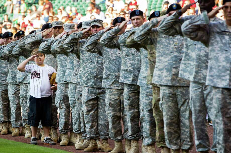 Tyler Snead salutes during the national anthem while he stands in a line of military personnel with his father, Sgt. John Snead of the 297th Inland Cargo Transfer Company at Fort Hood, at the conclusion of a parade to welcome home returning Iraq veterans, hosted by the City of Houston in conjunction with the Astros 2012 opening weekend game against the Colorado Rockies at Minute Maid Park on Saturday, April 7, 2012, in Houston. Photo: Smiley N. Pool, Houston Chronicle / © 2012  Houston Chronicle