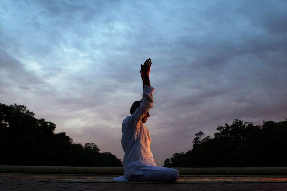 "Ratanlal Jaju, 89, of India, practices yoga in Hermann Park at sunrise Thursday, April 12, 2012, in Houston. Jaju, who gives two free lessons a day in his home town in India, was teaching his daughter and her friend (not pictured), while visiting his daughter in Houston. ""Yoga will increase your age and improve your health,"" Jaju said. ""You will live up to your God-given potential."" Photo: Johnny Hanson, Houston Chronicle / © 2012  Houston Chronicle"