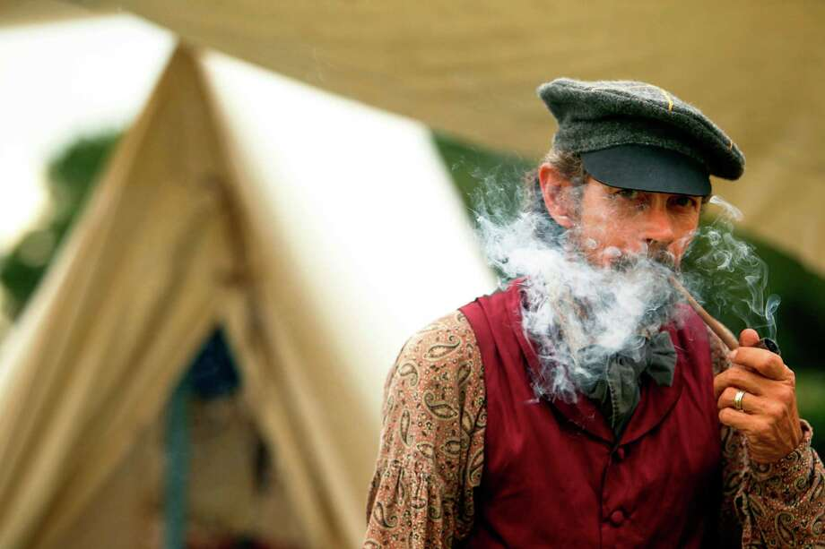 Jim Glover, dressed in period clothing, smokes a pipe outside his tent at the Texas Army civilian camp where history reenactors are setting up in preparation for the reenactment of the Battle of San Jacinto over the weekend on Friday, April 20, 2012, in La Porte. Photo: Mayra Beltran, Houston Chronicle / © 2012 Houston Chronicle