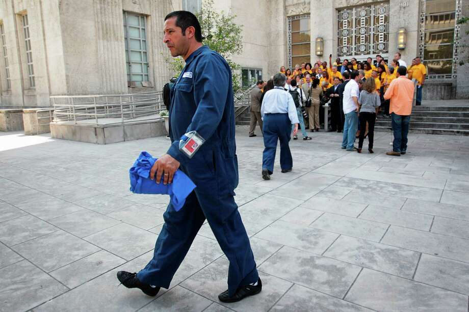 A Continental Airline employee walks past Southwest Airlines employees celebrating outside of City Houston after City Council Members approved a $100 million expansion of Hobby Airport, which is to build an International gate by 2015 on Wednesday, May 30, 2012, in Houston. Photo: Mayra Beltran, Houston Chronicle / Houston Chronicle