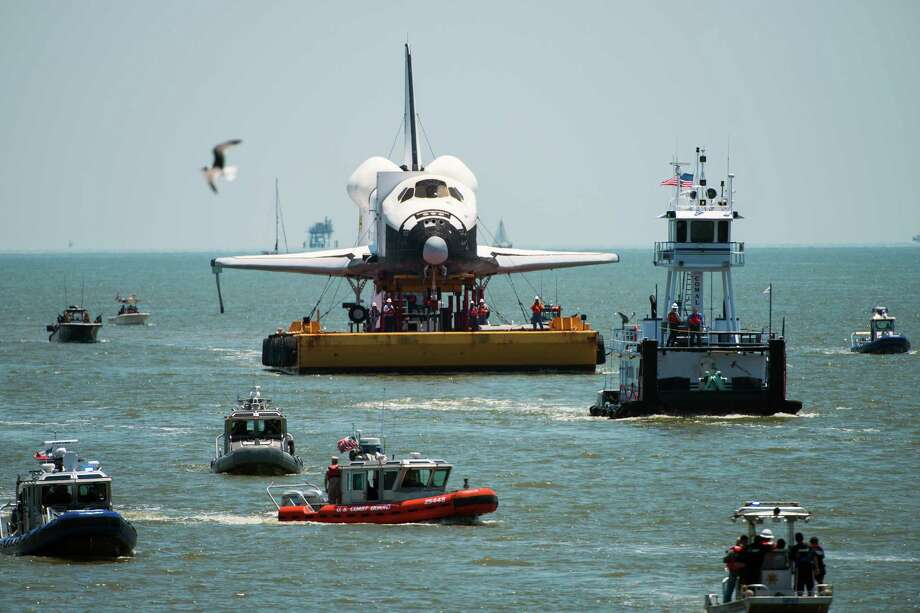 A full-size replica of the space shuttle is surrounded by boats as it passes the Kemah Boardwalk on Friday, June 1, 2012, in Kemah. The mock-up shuttle Explorer arrived by barge from the Kennedy Space Center to it's new home at Space Center Houston. Photo: Smiley N. Pool, Houston Chronicle / © 2012  Houston Chronicle