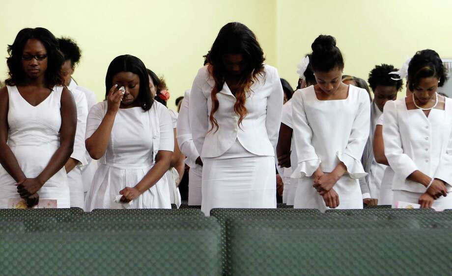 A women wipes away tears during a memorial service for sisters Jennifer Oluwatoyin Onita and Josephine Anita Onita, who were killed in a Nigerian plane crash, at the Redeemed Christian Church of God, Isaac Generation Saturday, June 9, 2012, in Houston. Photo: James Nielsen, Chronicle / © Houston Chronicle 2012