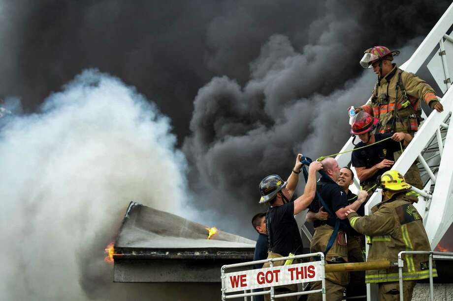 Houston firefighters help a fellow firefighter, who suffered heat exhaustion, off a ladder as they battle a multiple alarm blaze at a warehouse which stores oil spill clean-up products Thursday, June 14, 2012, in Houston. One firefighter was treated at the scene for heat exhaustion. Photo: Brett Coomer, Houston Chronicle / © 2012 Houston Chronicle