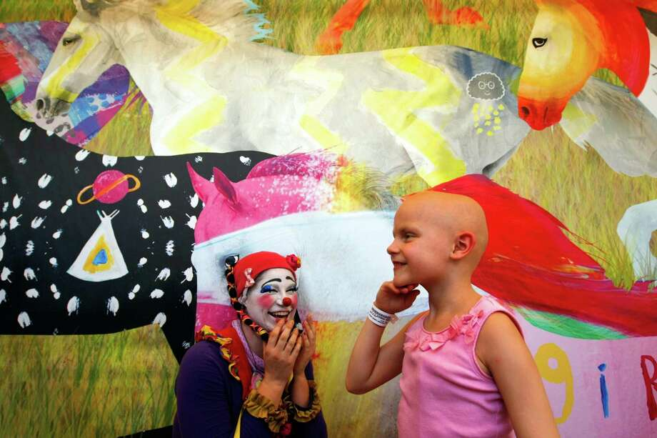 "Julia Cobb, 7, smiles next to Ringling Bros. and Barnum & Bailey circus clown, Genevieve ""G"" Flati after looking at the digital art mural of 25 horses titled ""Light, Hope, Wonder"", created by about 75 patients and their siblings. The mural was unveiled outside the MD Anderson Children's Cancer Hospital in the Texas Medical Center Thursday, July 26, 2012, in Houston. Photo: Johnny Hanson, Houston Chronicle / © 2012  Houston Chronicle"