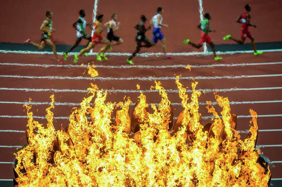 Runners pass beneath the Olympic flame during the men's 800-meter semifinals at the 2012 London Olympics on Tuesday, Aug. 7, 2012. Photo: Smiley N. Pool, Houston Chronicle / © 2012  Houston Chronicle