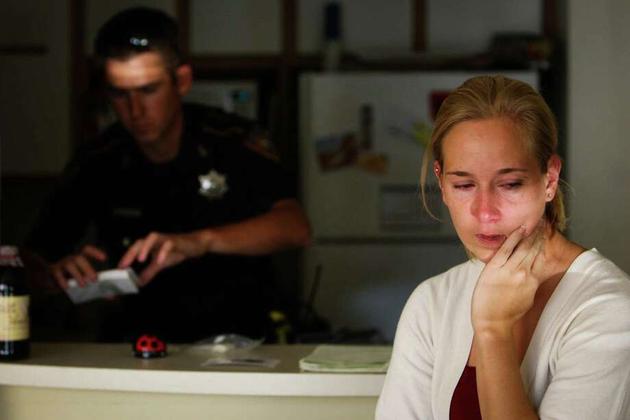 Harris County Sheriff Department Deputy Sean Simpson left, collects evidence at an apartment burglary as resident Julie Huerta sits nearby Thursday, Aug. 9, 2012, in Houston. Photo: James Nielsen, Chronicle / © Houston Chronicle 2012