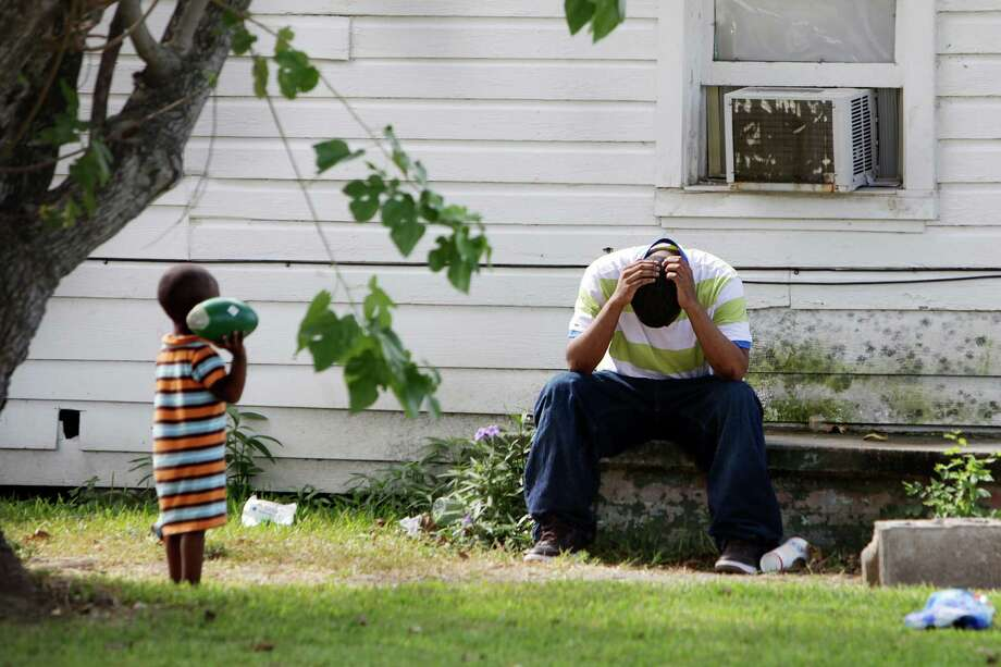 A family member sits outside the home where Houston Police investigate the death of a child found inside on Thursday morning in the 2300 block of Hutton near Quitman on Thursday, Aug. 16, 2012, in Houston.  HPD has not released any further information to what may have led to the death. Photo: Mayra Beltran, Houston Chronicle / © 2012 Houston Chronicle