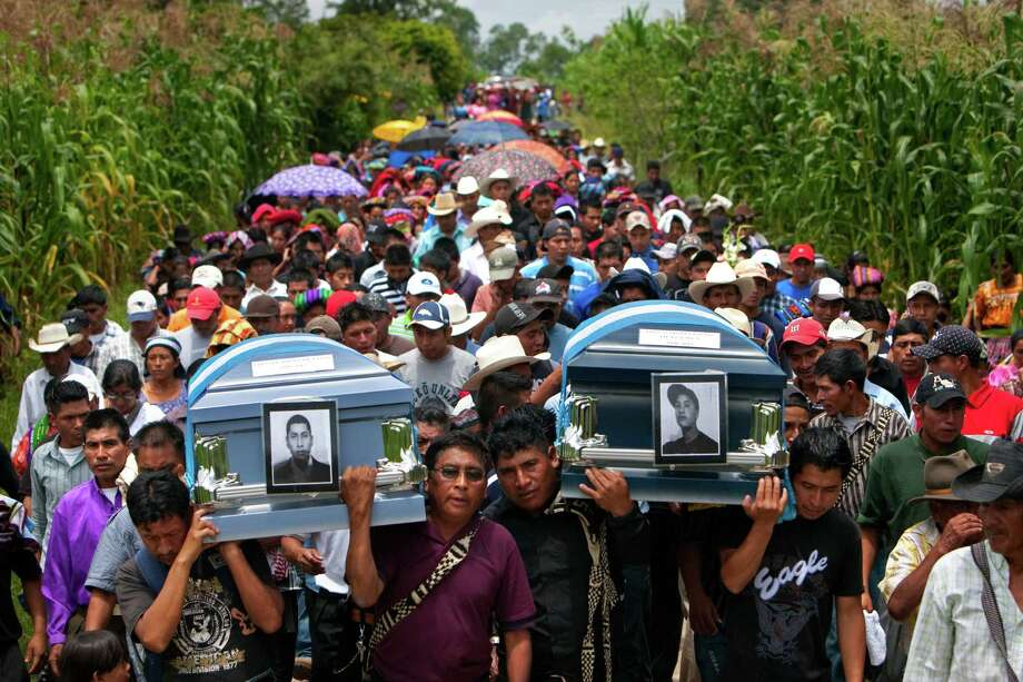 The caskets containing cousins Leonel Tipaz de Leon, 22, left, and Diego Mardoqueo Tipaz Jorge, 16, are carried on the backs of family, friends and neighbors as hundreds join the 2-mile journey along a steep and winding mountain road to a local cemetery Friday, Aug. 17, 2012, in Piedras Blancas, Guatemala. Leonel Tipaz de Leon, 22 and Diego Mardoqueo Tipaz Jorge, 16, died after a pickup truck carrying 23 people crashed outside of Goliad, TX July 22.  Fifteen people died in the accident. Photo: Johnny Hanson, Houston Chronicle / © 2012  Houston Chronicle