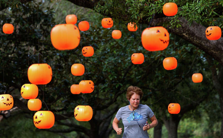 "Kim Mathis runs under plastic pumpkins hanging from trees in front of a home on University Blvd., Tuesday, Oct. 16, 2012, in Houston. The owner of the house said that over 100 plastic pumpkins hung from the trees. ""They're really cute,"" Mathis said. Photo: Cody Duty, Houston Chronicle / © 2012 Houston Chronicle"