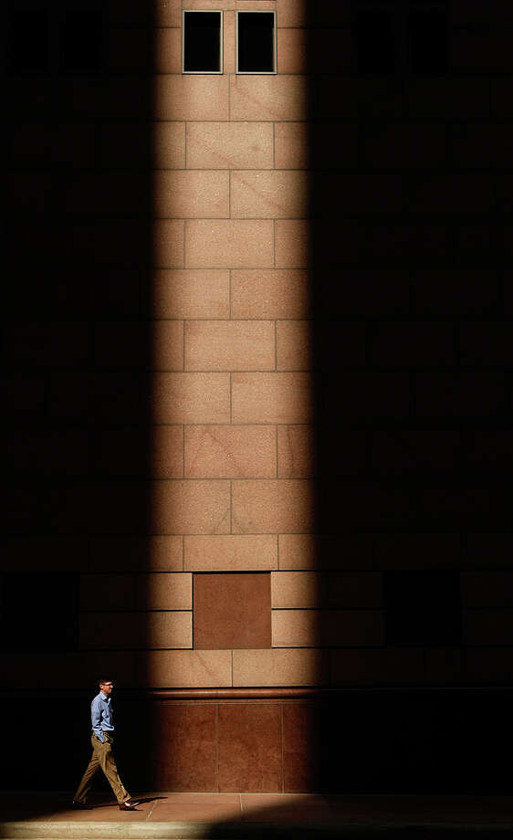 John Daniel walks through a shaft of light next to the Bank of America Center on his way to lunch Wednesday, Oct. 24, 2012, in Houston. Photo: Johnny Hanson, Houston Chronicle / © 2012  Houston Chronicle