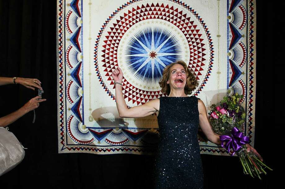 "Sherry Reynolds of Laramie, Wyoming reacts as she stands in front of her quilt ""America, Let it Shine"" after her quilt was announced as the Best of Show at the International Quilt Festival at the George R. Brown, Tuesday, Oct. 30, 2012, in Houston. Photo: Karen Warren, Houston Chronicle / © 2012  Houston Chronicle"