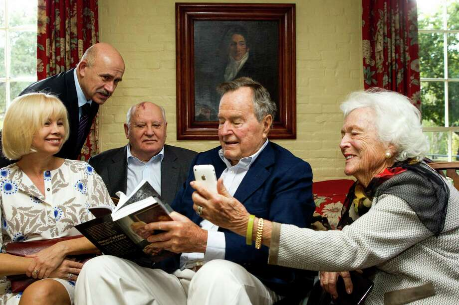Former first lady Barbara Bush, far right, and former President George H.W. Bush sit with Mikhail Gorbachev, former leader of the Soviet Union, his daughter, Irina Mikhailovna Virganskaya and Pavel Palazhchenko before having lunch together Thursday, Nov. 1, 2012, in Houston. Mrs. Bush is looking at photos of Virganskaya's children on her iPhone. Photo: Brett Coomer, Houston Chronicle / © 2012 Houston Chronicle