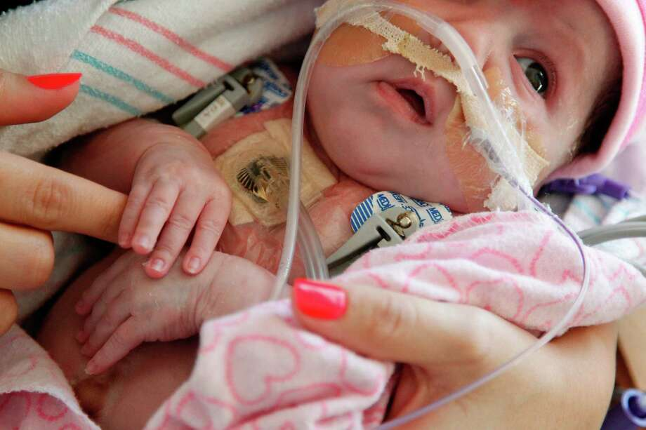 Audrina Cardenas, 6 weeks, holds her mother's finger while in her arms for the first time since she was born at Texas Children's Hospital on Thursday, Nov. 29, 2012, in Houston. Audrina Cardenas was born with part of her heart outside her chest. Photo: Mayra Beltran, Houston Chronicle / © 2012 Houston Chronicle