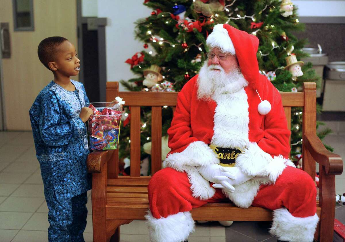 Five-year-old Troy Okhiria converses with Santa Claus during the annual Christmas party for Nigerian children of San Antonio at St. Matthew Catholic Church on Saturday night, Dec. 22, 2012. The event was sponsored by professional Nigerian immigrant women.