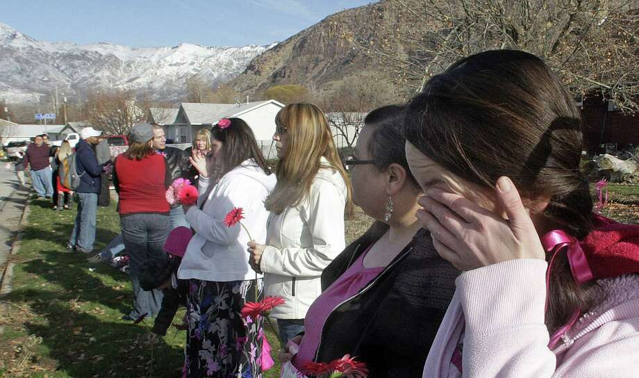 Mournier Claudia Wardle cries after the hearse carrying Emilie Parker passed by following funeral services for the 6-year old Connecticut elementary shooting victim, Saturday, Dec. 22, 2012, in Ogden, Utah.  Emilie, whose family has Ogden roots, was one of 20 children and six adult victims killed in a Dec. 14 mass shooting at Sandy Hook Elementary in Newtown, Conn. Photo: Rick Bowmer, (AP Photo/Rick Bowmer) / Associated Press