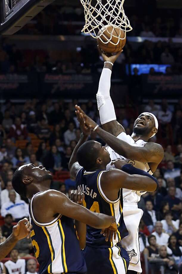 Miami Heat's LeBron James, right, shoots over Utah Jazz's Paul Millsap and Al Jefferson, left, during the first half of an NBA basketball game in Miami, Saturday, Dec. 22, 2012. (AP Photo/Alan Diaz) Photo: Alan Diaz, Associated Press